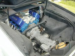 The V8 engine is nestled between the fender wells, partially buried under the tonneau shelf and normally covered by a lightweight molded piece designed to provide some luggage space.